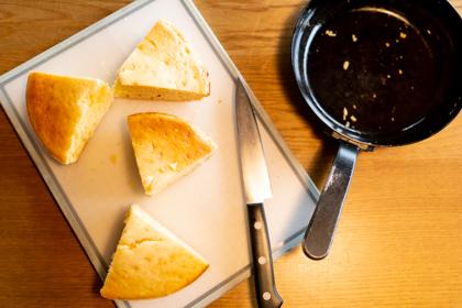 4つのピースに切り分け田ホットケーキがまな板の上に。右側にナイフと18cmフライパン