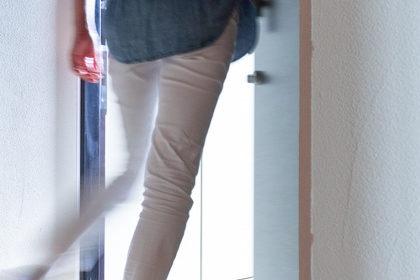 玄関の扉を開けて出ていく女性の背中